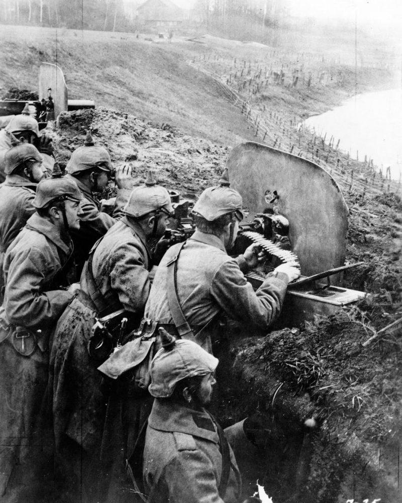 German infantrymen aim machine guns from a trench near the Vistula River in 1916